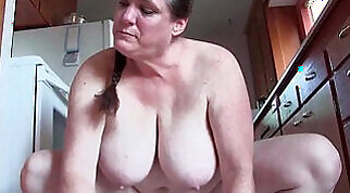 Busty Jackie Edge is posing naked in the kitchen and is filling a guy